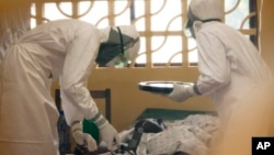 Dr. Kent Brantly (L) treats an Ebola patient at the Samaritan's Purse Ebola Case Management Center in Monrovia, Liberia.