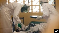 In this 2014 photo provided by the Samaritan's Purse aid organization, Dr. Kent Brantly, left, treats an Ebola patient at the Samaritan's Purse Ebola Case Management Center in Monrovia, Liberia.