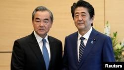 中國外長王毅在東京與日本首相安倍晉三握手。 (2019年11月25日)