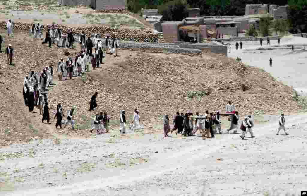 Afghan men carry the bodies of 7 civilians killed by a roadside bomb in the Alingar district of Laghman province, east of Kabul, Afghanistan, June 3, 2013.