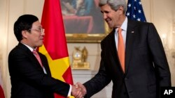 Secretary of State John Kerry shakes hands with Vietnamese Foreign Minister Pham Binh Minh as they speak to media at the State Department in Washington, Oct. 2, 2014, before having a working lunch. (AP Photo/Carolyn Kaster)