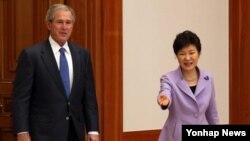 박근혜 한국 대통령이 3일 청와대에서 조지 부시 전 미국 대통령을 접견실로 안내하고 있다.