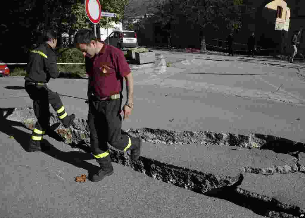 Firefighters inspect cracks in a road in Norcia, central Italy, after an earthquake with a preliminary magnitude of 6.6 struck central Italy, Oct. 30, 2016. Central Italy was hit by another powerful earthquake, toppling buildings that had recently withstood other major quakes and sending panicked residents back into the streets, but causing no immediate loss of life.