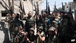 Syrian soldiers cheer after battling with rebels during a tour for journalists organized by the Syrian Information Ministry in the Damascus suburb of Jobar, Syria, July 14, 2013.