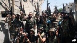ທະຫານລັດຖະບານຊີເຣຍ ພາກັນຮ້ອງໂຮດີໃຈ ລຸນຫລັງສູ້ລົບ ກັບພວກຕໍ່ຕ້ານ ໃນຂະນະທີ່ມີນັກຂ່າວຕ່າງປະເທດໄປເບິ່ງ ເຫດການ ທີ່ຈັດຂຶ້ນໂດຍກະຊວງຖະແຫລງຂ່າວ ຂອງຊີເຣຍ ໃນເມືອງ Jobar ເຂດຊານເມືອງຂອງນະຄອນ Damascus, ໃນວັນທີ 14 ກໍລະກົດ 2013.