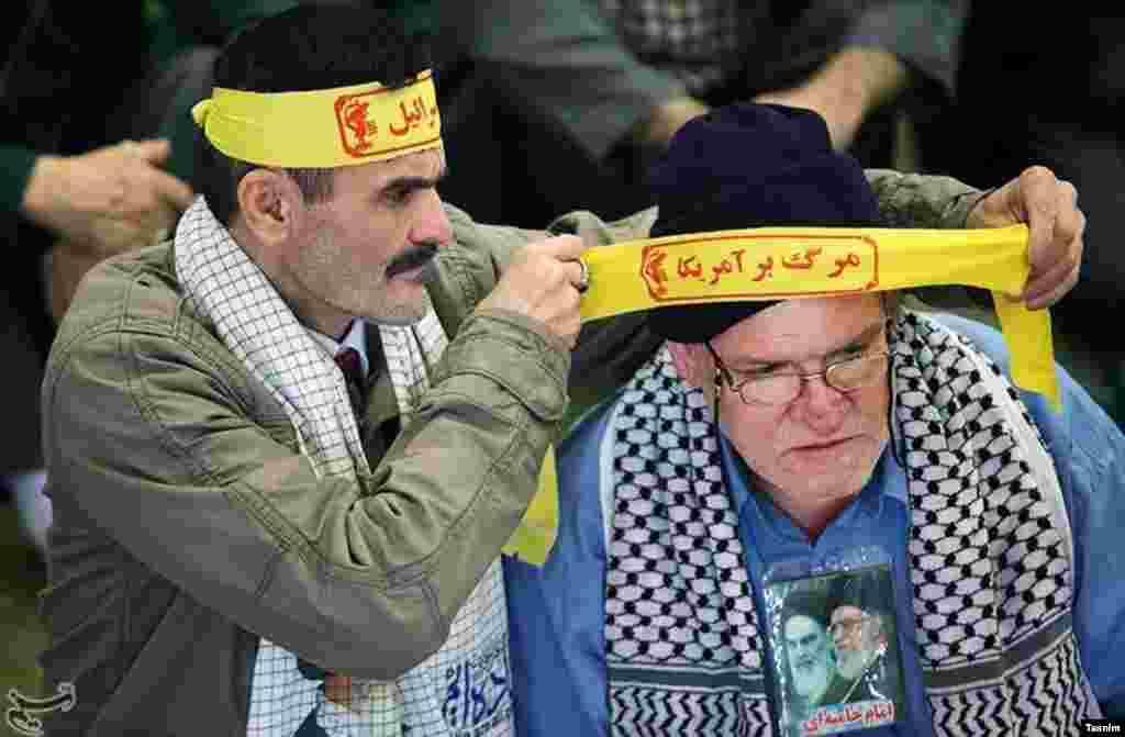 عکسی از نماز جمعه تهران و فرد سمت چپ که در رسانه ها به «آقای دوربینی شماره دو» است. او در نشست های مهم حضور میابد که دیده شود. در حال بستن سربندی با شعار «مرگ بر آمریکا» و خودش سربند مرگ بر اسرائیل دارد. عکس: مقداد مددی