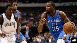 Kevin Durant (35) d'Oklahoma City à droite, tente un drible devant Al-Farouq Aminu (7) de Dallas Mavericks au cours de la prmière mi-temps d'un match de basketball, vendredi 10 octobre 2014, à Dallas, Texas
