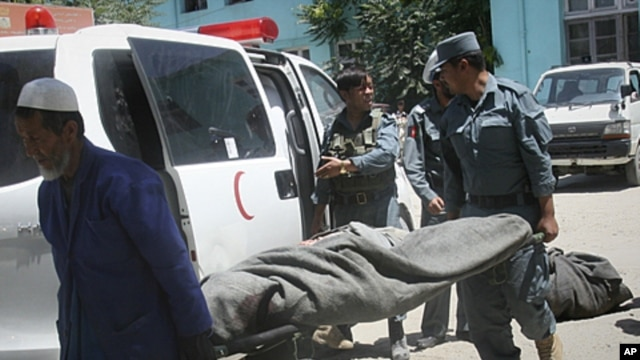 The lifeless body of a police officer is carried from an ambulance at the hospital in Ghazni, west of Kabul, Afghanistan, June 22, 2011.