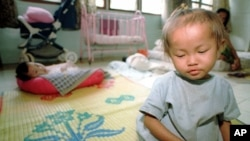 A young orphaned Cambodian infant girl infected with the HIV virus sits on a mat in the Phnom Penh Nutrition Center.