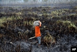 A fireman prepares to extinguish forest fire in Ogan Ilir, South Sumatra, Indonesia, Sept. 17, 2015.