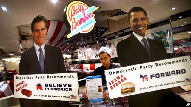 """Life-sized standees of U.S. President Barack Obama, right, and Republican presidential candidate and former Massachusetts Gov. Mitt Romney decorate the entrance of American Diner chain in Singapore, """"Billy Bombers"""" November 6, 2012."""
