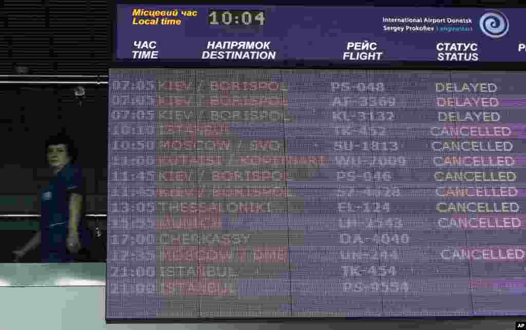 A worker walks past an information board displaying flight delays and cancellations at the international airport in Donetsk, May 6, 2014.