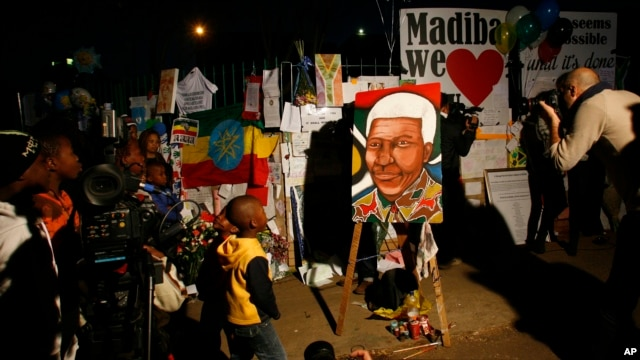 Children and their families stand outside the Mediclinic Heart Hospital where former South African President Nelson Mandela is being treated in Pretoria, South Africa, June 26, 2013.