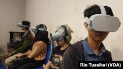 Sejumlah penyandang disabilitas dan non-penyandang disabilitas menyaksikan film melalui kacamata VR dalam 'The Feelings of Reality' di Bandung, Kamis (14/11/2019) siang. (VOA/Rio Tuasikal)
