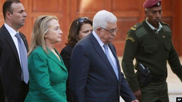 Menlu AS Hillary Rodham Clinton (kiri) didampingi Presiden Palestina Mahmoud Abbas menuju ruang pertemuan di Ramallah (21/11).