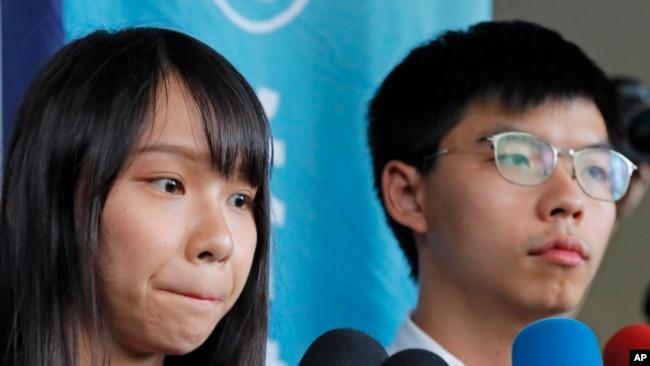 """前""""香港众志""""的秘书长黄之锋及成员周庭(左)在一家地区法院前对媒体讲话。(2019年8月30日)"""