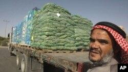 ایک فلسطینی سبزیوں کے ایک ٹرک کے پاس کیرم شلوم، جنوبی غزہ بارڈر کے پاس کھڑا ہے۔