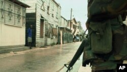 A Belize Defense Force officer guards a deserted street in Belize City. (File)