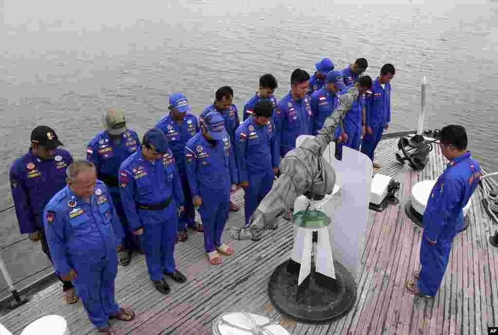 Lực lượng Cảnh sát biển Indonesia cầu nguyện trên một con tàu trước khi tiến hành hoạt động tìm kiếm và cứu hộ máy bay AirAsia tại đảo Sumatra, ngày 29/12/2014.