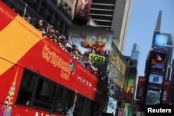 "Para turis menikmati suasana di Times Square, New York sebelum pandemi dengan menaiki bus wisata ""Sightseeing"" (foto: dok)."