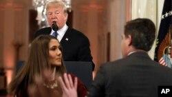 Predsednik Tramp posmatra dok pripravnica pokušava da uzme mikrofon novinaru CNN-a Džimu Akosti (Foto: AP/Evan Vucci)