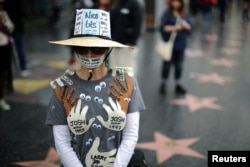 A woman who declined to give her name wears an outfit with the names of all the men in Hollywood she says sexually harassed her, during a protest march for survivors of sexual assault and their supporters in Hollywood, Los Angeles, California, Nov. 12, 2017.