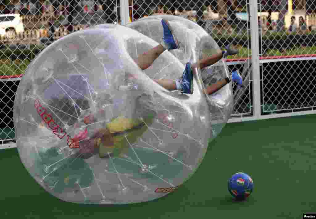 Players partially encased in giant plastic inflatable balls roll over on the ground, their legs in the air, during their bubble soccer match in Beijing, China.