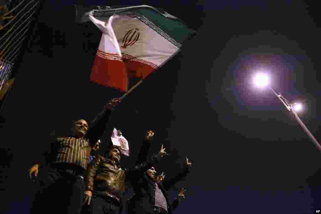 Iranians wave their national flag as they hold a poster of President Hassan Rouhani, while welcoming Iranian nuclear negotiators upon their arrival from Geneva in Tehran, Nov. 24, 2013.