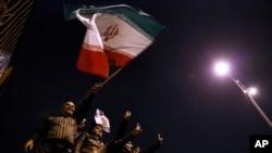 Na fotografiji Iranske studentske novinske agencije vide se gradjani kako mašu zastavom pozdravljajući povratak iranskih pregovarača iz Ženeve.
