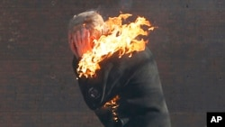 An anti-government protester is engulfed in flames during clashes with riot police outside Ukraine's parliament in Kyiv, Feb. 18, 2014.