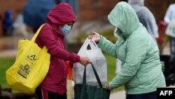 매릴랜드주 코키스빌에서 '볼티모어 헝거 프로젝트'의 자원봉사자가 도움이 필요한 사람들에게 식료품 가방을 전달하고 있다. (자료사진)