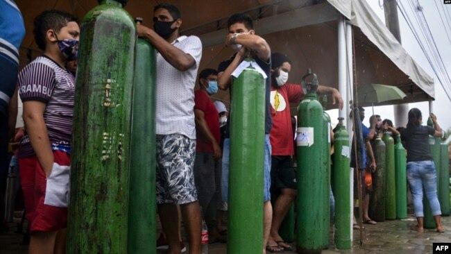 Familiares de pacientes con COVID-19 hacen cola durante largas horas para recargar sus tanques de oxígeno en Manaus, estado de Amazonas, el 19 de enero de 2021.