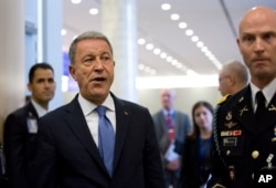 FILE - In this Wednesday, June 26, 2019 file photo, Turkish Defense Minister Hulusi Akar, center left, arrives to NATO headquarters in Brussels.