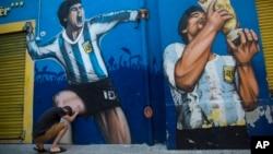 Seorang penggemar, Augusto Canosa, berdoa sambil menyentuh lukisan Diego Maradona dekat stadion Boca Juniors di Buenos Aires, Argentina, 27 November 2020.
