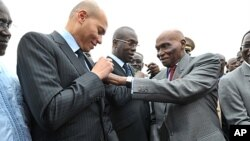 Senegalese President Abdoulaye Wade (R) adjusts a ribbon on his son's jacket, Karim Wade, in 2011. Police in Senegal have said they will question Karim Wade as part of bribery investigations.
