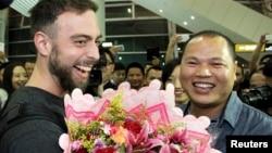 "Penulis BuzzFeed Matt Stopera (kiri) dari AS disambut oleh ""Brother Orange"" dari China di bandara di Jieyang, provinsi Guangdong, 17 Maret 2015."