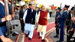 In this photo released by Press Information Department, India's Prime Minister Narendra Modi, right, reviews a guard of honor with his Pakistani counterpart, Nawaz Sharif, in Lahore, Pakistan, Dec. 25, 2015.