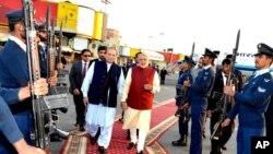 នាយករដ្ឋមន្រ្តីឥណ្ឌាលោក Narendra Modi (ខាងស្តាំ) ដើរជាមួយនឹងនាយករដ្ឋមន្រ្តីប៉ាគីស្ថានលោក Nawaz Sharif នៅក្រុង Lahore ប្រទេសប៉ាគីស្ថាន នាថ្ងៃទី២៥ ខែធ្នូ ឆ្នាំ២០១៥។
