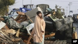 A Japanese woman draped in a blanket stands in the rubble from Friday's quake and tsunami, Sunday, March 13, 2011.