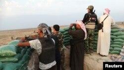 Pejuang dari suku di Irak membawa senjata dalam pertempuran dengan ISIS di kota Amriyat al-Falluja, provinsi Anbar (31/10).