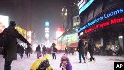 ພວກເດັກນ້ອຍ ພາກັນຫລິ້ນຫິມະ ທີ່ຈະຕຸລັດ Times Square ໃນລະຫວ່າງພາຍຸຫິມະ ເມື່ອວັນພະຫັດ ທີ 2 ມັງກອນ 2014.