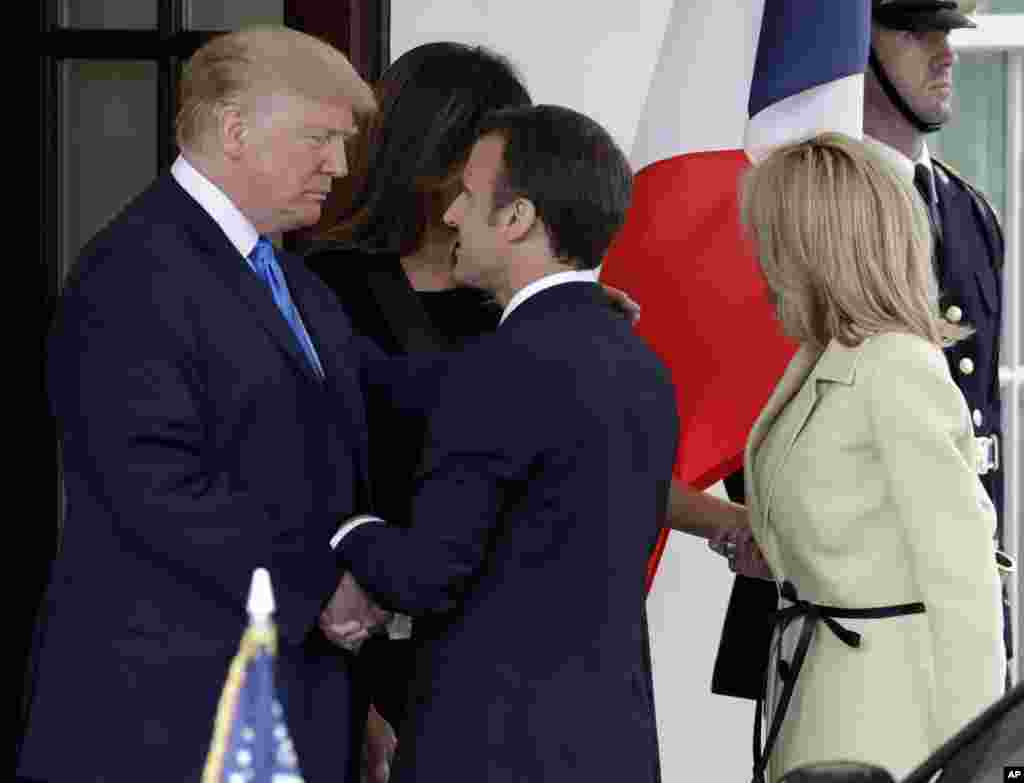 President Donald Trump and first lady Melania Trump greet French President Emmanuel Macron and his wife Brigitte Macron at the White House, April 23, 2018, in Washington.