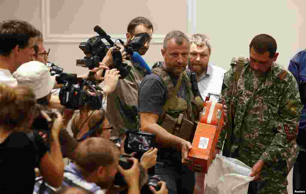 A pro-Russian separatist shows members of the media a black box belonging to Malaysia Airlines flight MH17 before its handing it over to Malaysian representatives in Donetsk, Ukraine.