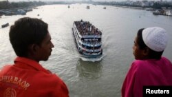 FILE - An overcrowded passenger boat navigates through Buriganga River as people watch from a bridge in Dhaka, Bangladesh, July 27, 2014.