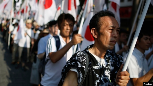 "Members of the nationalist movement ""Ganbare Nippon"" holding Japanese national flags march while paying tribute to the war dead near Yasukuni Shrine in Tokyo, August 15, 2013, on the 68th anniversary of Japan's surrender in World War II."