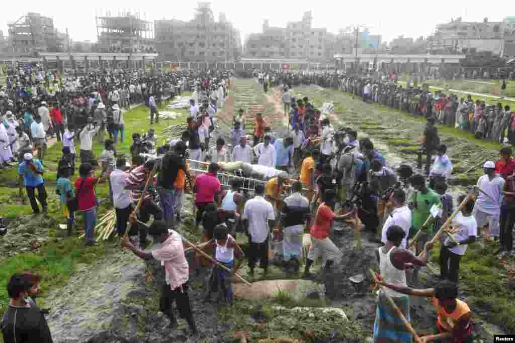 Workers dig mass graves during a burial of unidentified garment workers, who died in the collapse of the Rana Plaza building in Savar, Bangladesh, May 1, 2013.