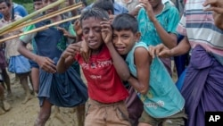 Rohingya Muslim boys, who crossed over from Myanmar into Bangladesh, cry as Bangladeshi men push them away during distribution of food aid near Balukhali refugee camp, Bangladesh, Sept 20, 2017.