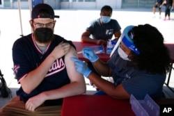Chandler Millard, kiri, dari Alexandria, menerima vaksin Johnson & Johnson di klinik vaksinasi COVID-19 yang diselenggarakan oleh Washington Nationals sebelum pertandingan bisbol melawan Colorado Rockies, 9 September. 18, 2021. (Foto: AP)