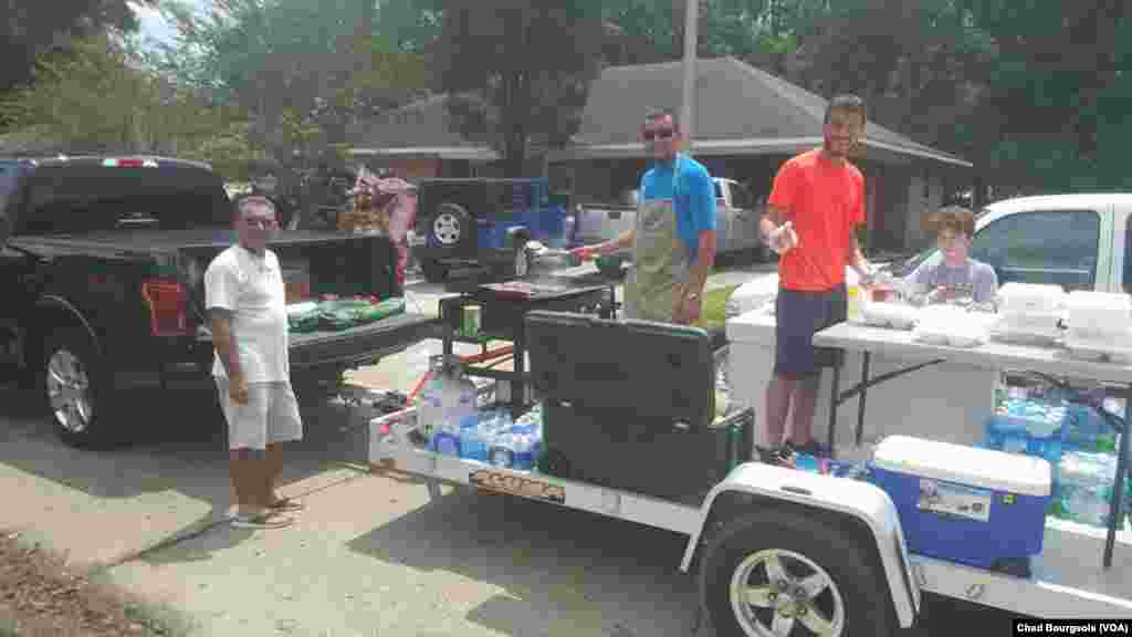 At least one crew of volunteers has been traveling around St. Amant on a trailer with coolers full of food and a working grill, delivering fresh meals.
