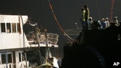 FILE - Workers salvage boat which sank after colliding with ferry near Lamma Island off the southwestern coast of Hong Kong, Oct. 2, 2012.